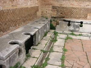 """Een Romeinse latrina in Ostia. In het Italiaans en Frans worden openbare """"pissoirs"""" naar Vespasianus genoemd (vespasienne en vespasiano, respectievelijk) ter herinnering aan zijn belasting op openbare toiletten."""