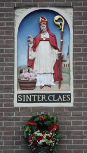 16e eeuwe afbeelding van Sint-Nicolaas in Amsterdam, nog zonder baard maar wel met een anachronistische mijter. De Sint is beschermheilige van Amsterdam, die 4 Nicolaaskerken bevat.