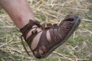 """De door Romeinse soldaten gedragen caliga, de stevige kruising tussen laars en sandaal, beslagen met ijzeren noppen tegen slijtage van de zool. In het Latijn geldt het gebruik van """"ul"""" als op-één-na-laatste lettergreep als verkleinwoord (""""-tje""""). Caligula betekent dus """"soldatenschoentje""""."""