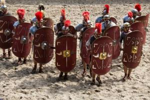 De cunium of wig-formatie (hier uitgevoerd door Legio II Augusta, die Vroeg-keizerlijke soldaten voorstellen) is zo effectief voor het doorbreken van vijandelijke linies, dat zelfs de moderne ME hem nog toepast.