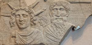 Sol Invictus, herkenbaar aan de zonnekroon op zijn hoofd. De oude man naast hem zou Jupiter kunnen zijn. Achter hen de maangodin, herkenbaar aan haar maan-diadeem.