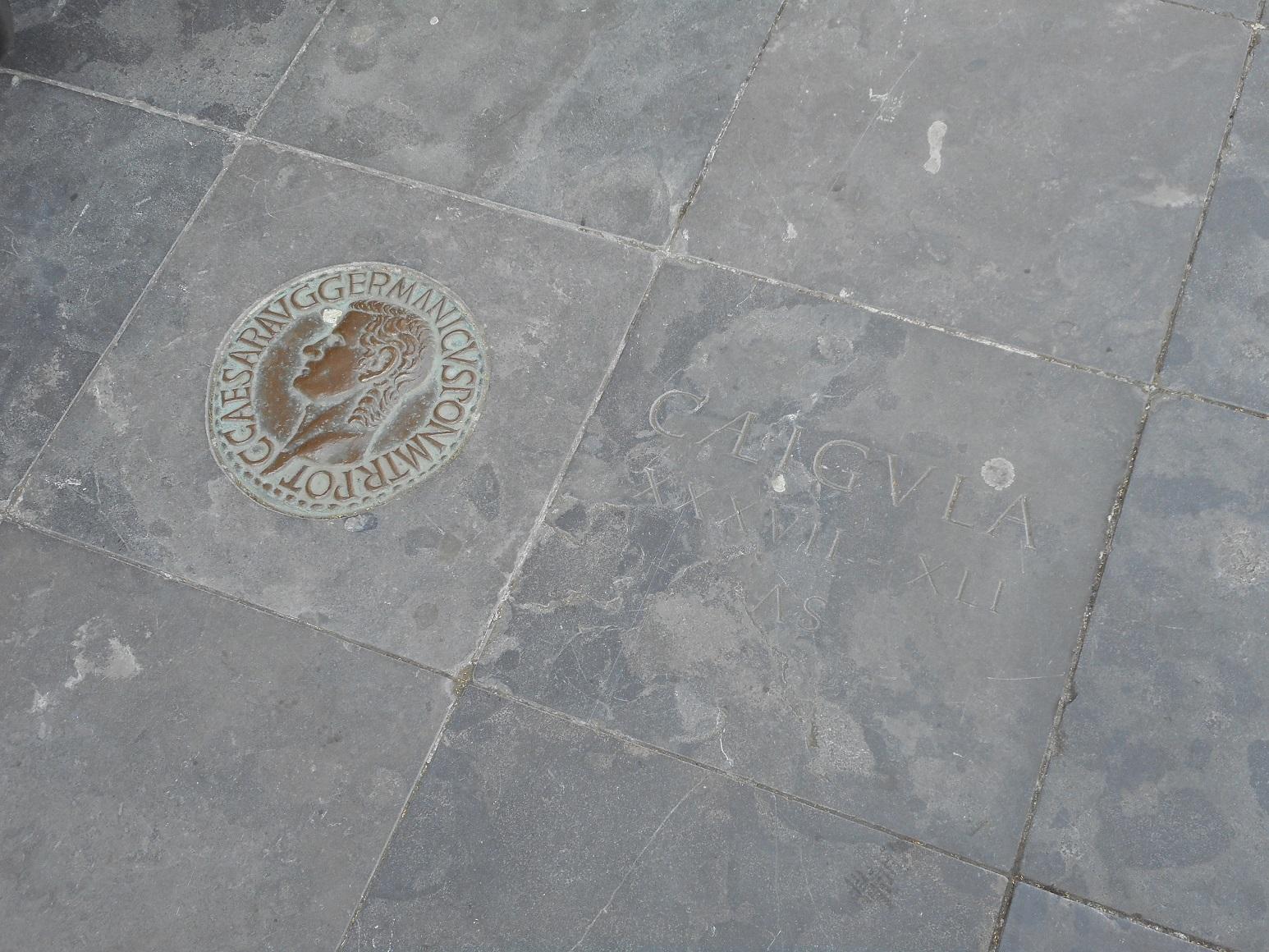 Replica van een Romeinse munt van Caligula op het Rijnplein in Alphen.